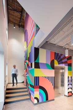 Stairs wrapping an elevator shaft Office Graphics, Dynamic Painting, Mural Wall Art, Environmental Graphics, Rug Shapes, Creative Studio, Office Interiors, Visual Merchandising, School Design