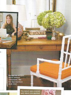 white bamboo chair with orange cushion