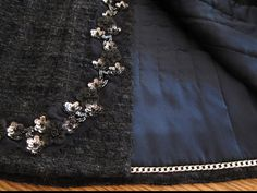 love the sort of raven-shaded black fabric, and REALLY love the trim chosen here.