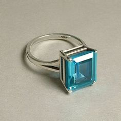 A Breathtaking Estate Vintage Blue Topaz Aquamarine Solitaire Ring featuring an Emerald-Cut (over 4.0 Carat) Cubic Zirconia in a Spectacular Green Blue Color, High Raised Setting in Solid Sterling Silver, Split Shank, Hallmarked .925 with a Makers Mark, Weight 4.0 Grams, Size 8, circa 1980s!  Measurements: Ring Size 8. Face is 7/16 in length by 3/8 in width (11mm by 9.5mm). Shank is 3/16 and tapers to over 1/16 in back. Side depth is 5/16.  This Emerald Cut Ring has a...