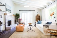 Two living room poofs and a massive white couch add the perfect light and bright touch for this big living room