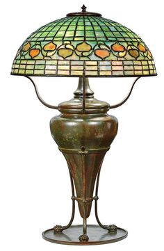 <b>Tiffany Studios Bronze and Favrile Leaded Glass Leaf and Vine Lamp  </b> <br /> <i>Circa</i> 1910-15 <br /> The domed shade comprised of six geometric bands in mottled semi-opaque green and white slag glass, continuing to a lower section with a meandering ivy vine issuing alternating upright or downturned leaves in mottled amber, orange and green acorn-shaped leaves, tag stamped <i>TIFFANY STUDIOS NEW YORK</i>, on a canister urn-form base contained within a ring-shaped mount supported by…