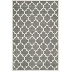 Anchor your living room seating group or define space in the den with this hand-tufted wool rug, featuring a quatrefoil trellis motif for eye-catching appeal.