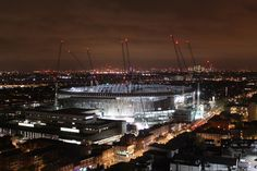 2018-04-24: Tottenham Hotspur Stadium at night. The roof support structure is in place and the roof surface construction has just begun.