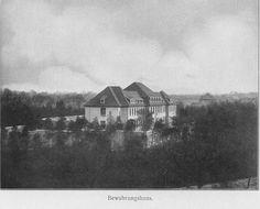 Schwarz-Weiß-Foto: Haus mit einer Mauer und vielen Bäumen rundherum