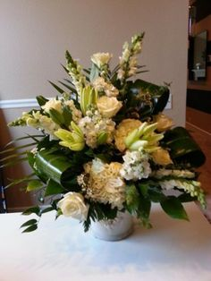 Beautiful All White Arrangement with Lilies, Snapdragons, Stock, Roses and Hydrangeas Done in a Contemporary Way. Perfect for Sympathy Piece to a Home or to the Service.