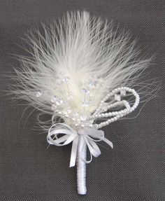 http://www.sarahsflowers.co.uk/wpcms/wp-content/uploads/2013/11/Delicate-Buttonhole-Feathers-Crystals-Beads-and-Pearls-JR2_4128.jpg