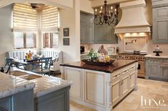 Paradise Valley Home Feels Collected, Not Designed - The Kitchen: Dyer finished the kitchen's knotty alder wood cabinets in a soft blue-green stain. A custom banquette creates a cozy dining nook in the corner along with blue distressed-wood armchairs.