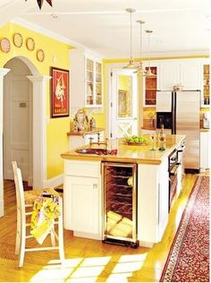 Yellow and white kitchen:  Balanced with red accents to make it not so overwhelming.  This is exactly what I want our kitchen to be. Maybe at some teal colored touches too.