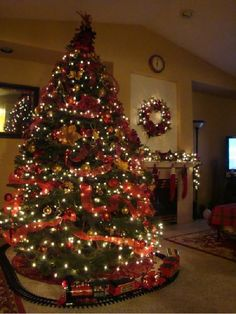 Putting the train around the Christmas tree, my favorite Christmas decoration. This room is gorgeous.
