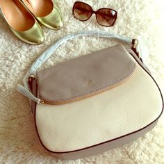 """Pebble grey cream ivory handbag purse satchel bag This authentic, genuine cowhide leather, pebble white/warm putty grey kate spade handbag is the perfect blend of classical styling and modern hue. The rounded bottom adds playfulness to the elegant structure. Features include 14k gold hardware, magnetic front closure, curved top handle, detachable shoulder strap, custom woven lining, three interior pockets, top zip pockets, and back exterior pocket. Approx. dimensions: 12.5"""" x 10"""" x 4"""" Drop…"""