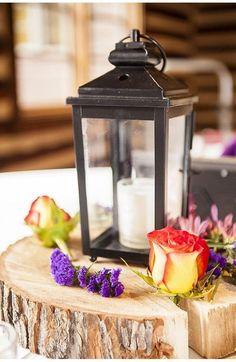 lanterne avec bouges blanche et fleurs délicates arrangées sur une rondelle de bois
