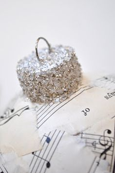 Homemade christmas ornaments! Wrap clear glass ball with music paper. To make it sparkle add clear glitter.
