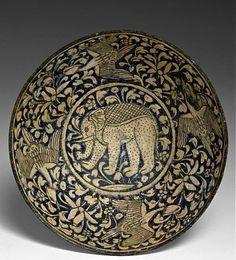 AN ILKHANID CERAMIC BOWL UNDERGLAZE-PAINTED WITH AN ELEPHANT, 13TH-14TH CENTURY…
