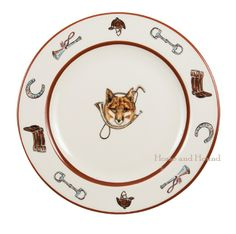 Foxhill Manor Dinnerware. Everyday tableware features a fox and horn design bordered by an equestrian theme including hunting horns, boots, horseshoes and bits. Trimmed in rich brown. Made in Portugal for C.E. Corey.