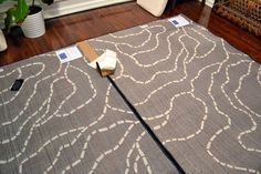 How to Save Money on Large Area Rugs - turn two smaller rugs into one large one with carpet tape.