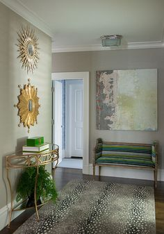 Contemporary gray and gold foyer boasts an antelope rug positioned on wood floors in front of a green and gold foyer…