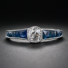 Here is a striking variation on a traditional diamond engagement ring. A beautiful antique cushion diamond, weighing .80 carats, is dramatically accentuated with a tapered row of French-cut calibre sapphires running down the top half of the ring shank. Both the diamond and sapphires are outlined with fine platinum milgraining in this sleek and dramatic Art Dec original, circa 1920s.