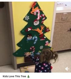 """Children's Christmas tree. Felt Christmas tree which is mounted to the wall. Felt """"ornaments"""" have Velcro attaches at the back and can be attached to and moved on the Christmas tree by the child. Felt Christmas, Christmas Stockings, Felt Ornaments, Holiday Decor, Entrepreneurship, Student, Children, Wall, Needlepoint Christmas Stockings"""