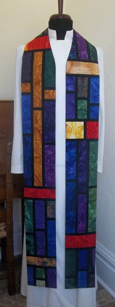 To see my full selection, please go to www.SerendipityClergyStoles.com   This handmade stained glass clergy stole features a gold cross on the wearers right, offset by a variety of batik prints in liturgical greens, purples and blues, and accented with other gold and red prints, which give the design a dynamic and celebratory mood. It is appropriate for Ordinary Time, and can also be used as a multi-purpose stole during other seasons as well. This is a wonderful gift for a pastor who only…