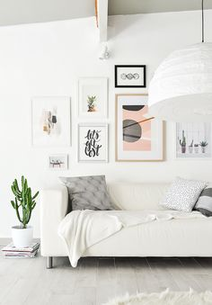 Bright white living room with a gallery wall, a simple sofa, and a large paper lantern