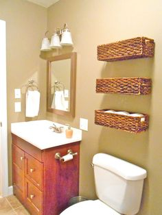 Guest bathroom look. Wicker baskets nailed to wall.