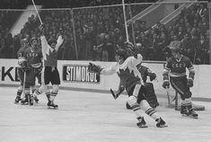 Paul Henderson (with helmet) and Bobby Clarke celebrate Henderson's series-winning goal in Game 8 of the 1972 Summit Series between Canada a...