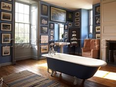 Blue freestanding rolltop bath in sunlit bathroom with artwork  Georgian townhouse  Laughame  Wales
