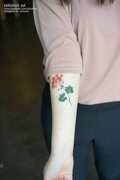 Geranium tattoo on the right inner forearm.