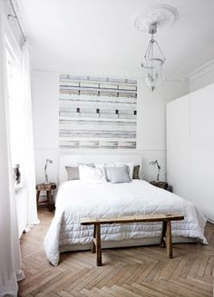 White bedroom with rustic/salvaged wood elements and chevron floors.