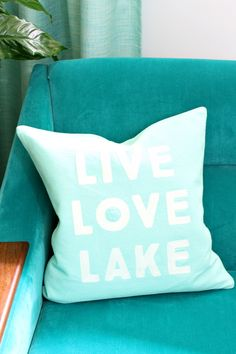 Live love lake turquoise lakehouse cottage beach pillow on teal velvet mid century modern chair
