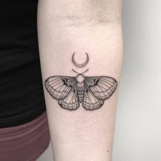 Small moth tattoo on the inner forearm.