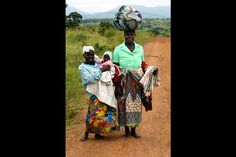 A woman in Chimoio, Mozambique, carries her belongings home on her head accompanied by her daughter, who carries a younger sibling. Lacking cars or even bicycles, many African women must go on foot and carry their burdens. (February 2002)