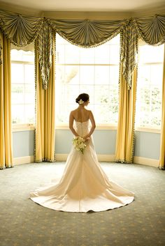 bride standing in front of beautiful bay windows in ivory a-line dress wearing a ivory floral hairpiece and holding white and green bouquet behind her back - photo by North Carolina based wedding photographers Cunningham Photo Artists