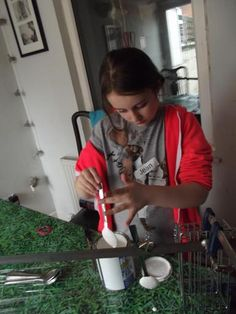 My 9 year old carefully dipping spoons in metal paint to make garden and pot ornaments