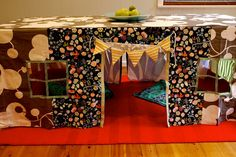 Under the dinning table cubby house! Perfect for a rainy day! This would be great to make with all my leftover scraps of fabric.