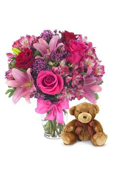 A teddy bear makes a nice addition to a lovely floral bouquet ♥