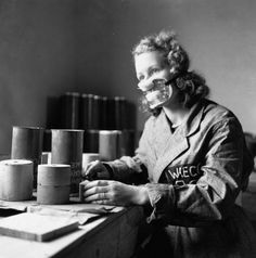 1941: A woman employed in a government factory at work filling smoke flares for the RAF. She wears a mask for protection against injurious gases. (Photo by Keystone Features/Getty Images) ~