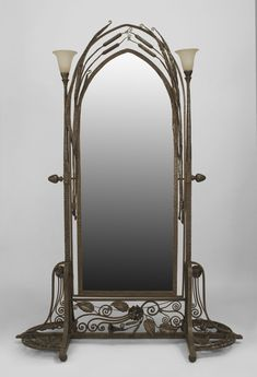 French Art Deco wrought iron cheval mirror with arch design beveled glass surrounded by cattails & side columns with art glass shades on a f...