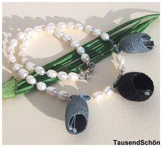 Perlencollier der besonderen Art:  Süßwasserperlen mit Blüten  aus Seidenkokon in schwarz und  grau, aus den Kokons hängen Blütenstiele, an denen klei