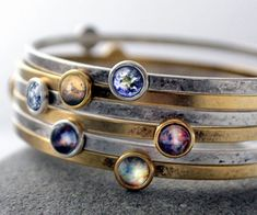 Carry the majesty of the cosmos on your wrist by accenting your outfit with this stunning galaxy space bracelet. This handmade item comes adorned with small pendants that each feature a vivid design depicting galaxies and planets in our universe.