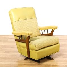 This mid century modern rocker is upholstered in a durable shiny light yellow green vinyl. This rocking chair has a high back, carved walnut wood accents and a rocking swivel base. Eye catching armchair perfect for a stylish nursery! #americantraditional #chairs #rockingchair #sandiegovintage #vintagefurniture