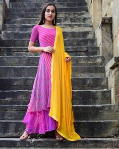 It has a boat neck with double layered flared with elbow sleeves.It comes with yellow dupatta having a patch of gotta patti and gota lace-up to and 1 side pocket. Dry Clean only. Chiffon with cotton lining Indian Gowns, Indian Attire, Indian Wear, Indian Outfits, Kurti Designs Party Wear, Kurta Designs, Blouse Designs, Chudidhar Designs, Bandhani Dress
