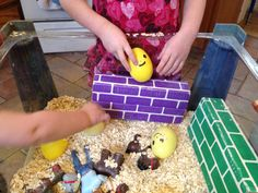 Humpty Dumpty Sensory Table with oats, large plastic eggs with faces drawn on (Humpty Dumpty), horses, cardboard brick (wall), and men.