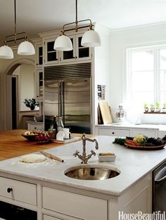 A small corner sink is inset into the butcher-block-and-marble island in a French Country-style kitchen in Connecticut.