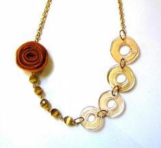 Collar corto (15cm.), el diámetro es de 30cm.  Es una gargantilla realizada con cadena dorada, cuentas facetadas de cristal en color ocre y aros de cristal. Viene rematada con una flor tejida, a juego con las piedras naturales.