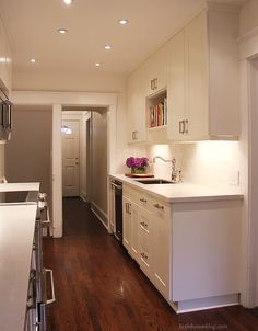 Fabulous galley kitchen with cloud white cabinet doors paired with modern polished nickel hardware.