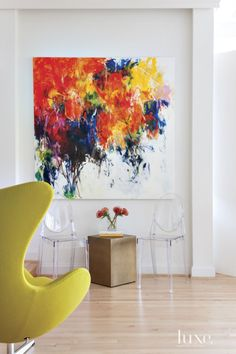 In the living room, white walls showcase a vibrant oil painting, Forgetful Summer Paints Landscape by Elena Baker, from UGallery. The metal-cube side table is from West Elm; the chartreuse Egg chair is from Design Within Reach.