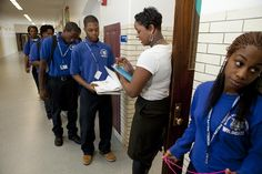 A teacher at Wendell Phillips Academy High School, in Chicago, greets students at the door to her classroom and checks that they have their class supplies, in 2011.