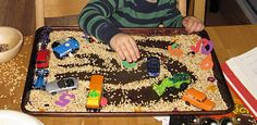 Strange as it may seem, tray of unused rice and a few cars keeps New Kid occupied, plus it's a fun sensory activity.